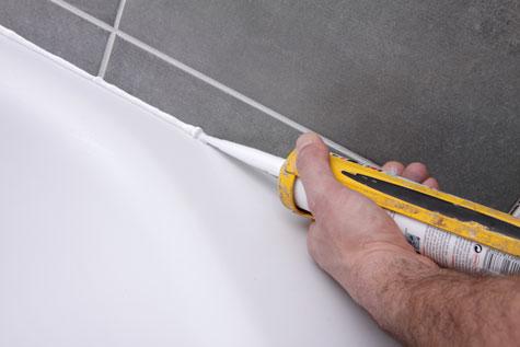 Pose de joint de silicone dans une salle de bain